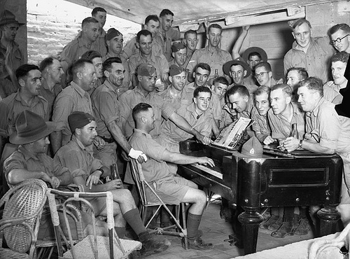 A large group of American WWII soldiers gathered around an old piano